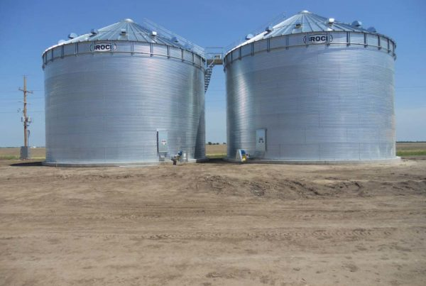2 large metal grain bins next to a field