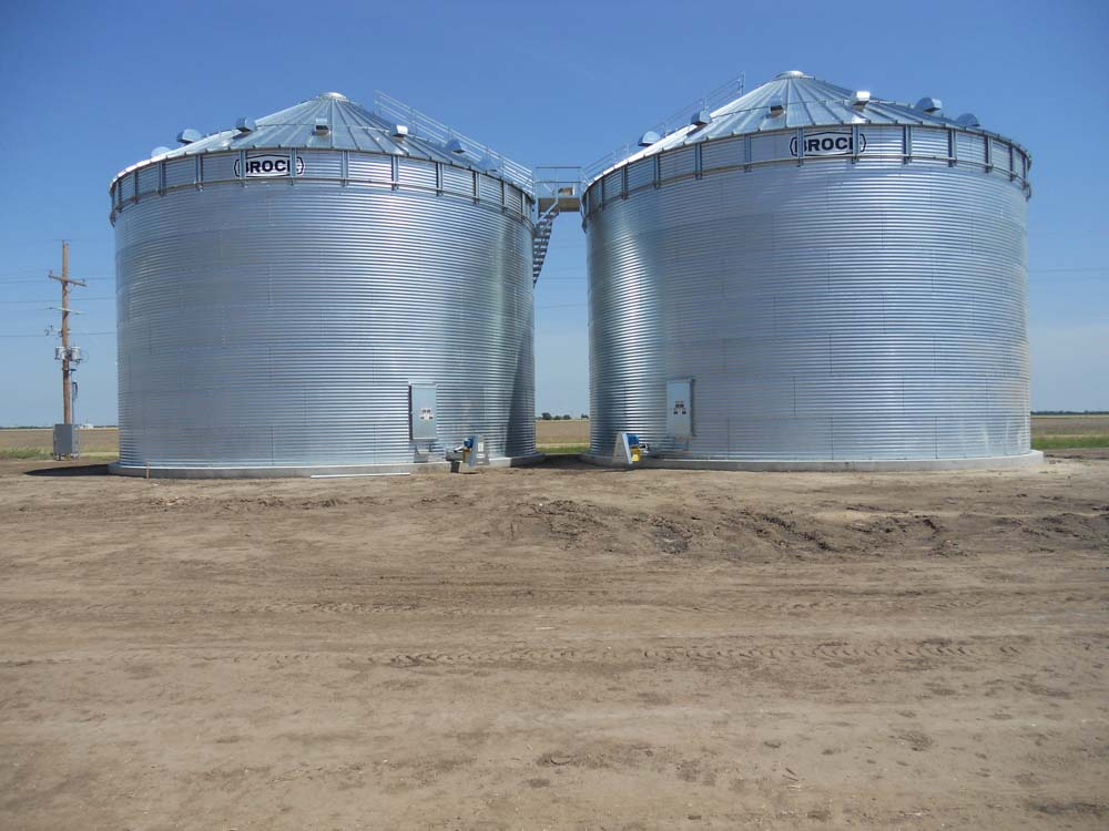 2 large metal grain bins next to a field
