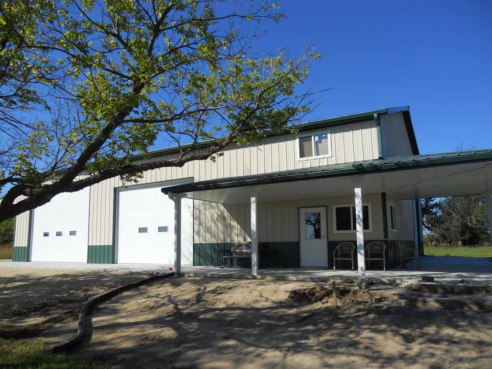 Tan and green metal building with a covered porch and 2 large overhead doors