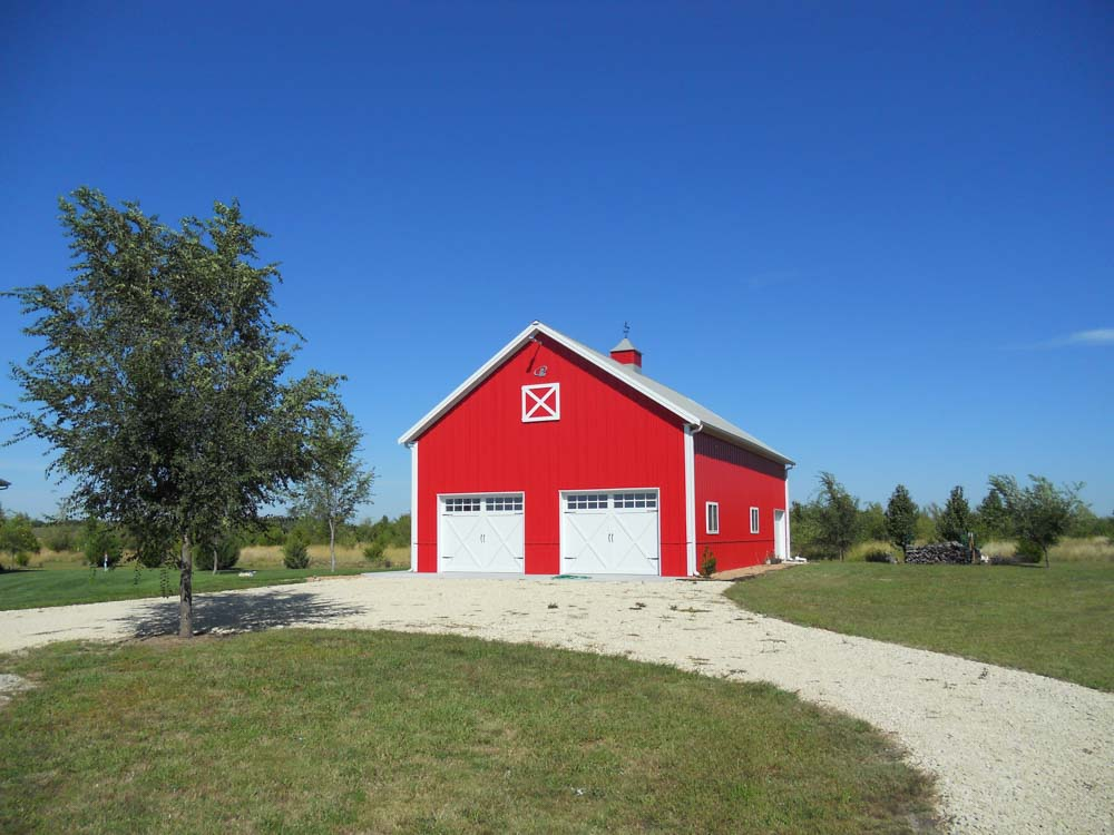 Red metal barn with two garage doors and a circle gravel drive