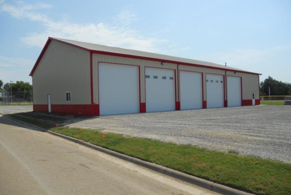 Tan and red metal building with 5 large overhead doors