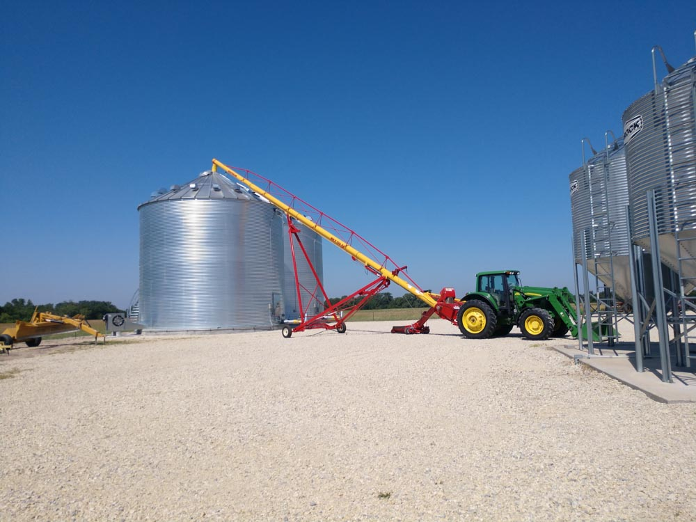 Tractor using auger to move grain into large metal grain bin