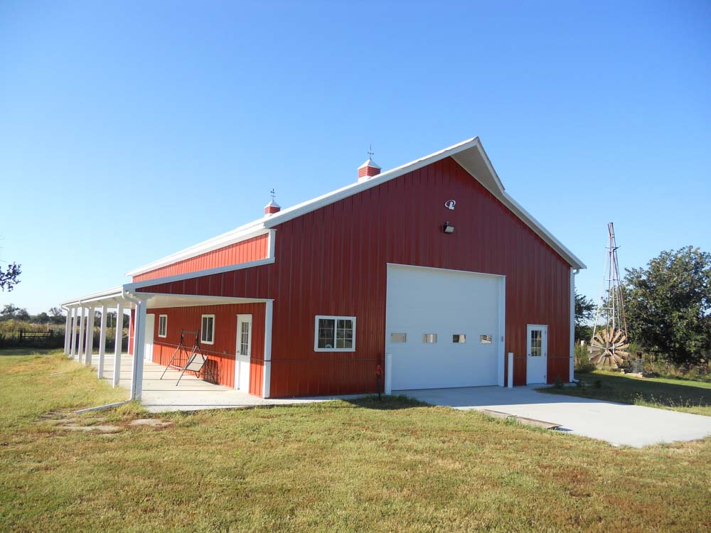 Red metal barn with covered porch and large overhead door